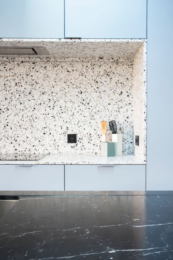 an airy blue kitchen with a niche done with terrazzo and a black marble kitchen island shows the beauty of materials