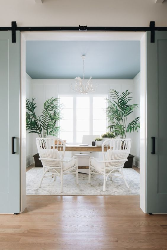 an airy coastal home office with a blue ceiling, a wooden desk, white rattan chairs, potted plants and a beautiful chandelier