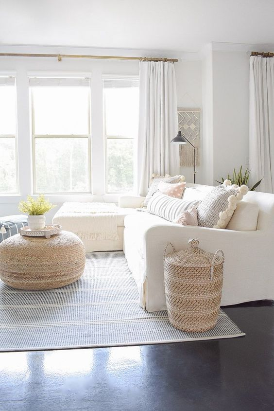 an airy summer living room with a white sectional, a woven ottoman and a basket for storage, a macrame piece and neutral textiles