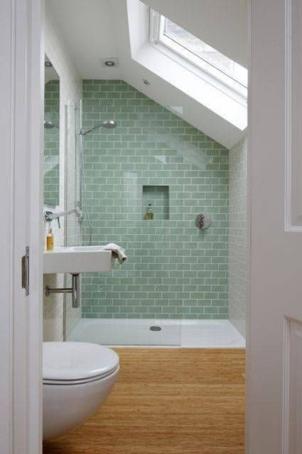 an attic bathroom with a bamboo floor, a skylight, green tiles in the shower and white appliances is chic