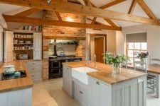 an attic kitchen with wooden beams, a large stove, grey cabinetry, a brick wall and butcherblock countertops is chic