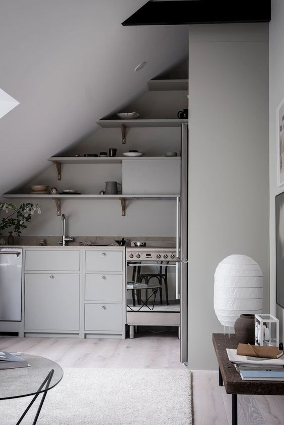 an attic minimalist kitchen with grey walls and cabinetry, open shelves and stone countertops plus some tables