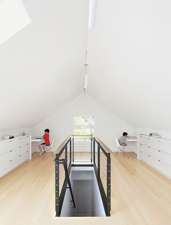 an attic shared study space with bamboo floors, white cabinets for storage and floating desks feels airy and light