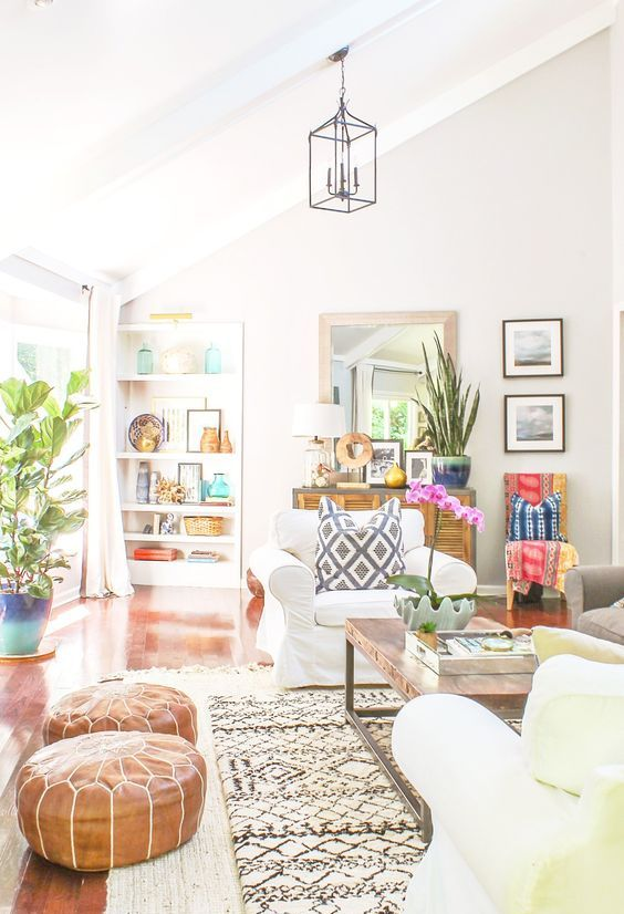 an eclectic summer living room with built-in shelves, layered rugs, leather poufs, creamy chairs, colorful textiles and potted plants