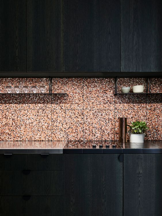 an elegant black kitchen with black countertops and a terracotta-colored terrazzo backsplash is bold and cool