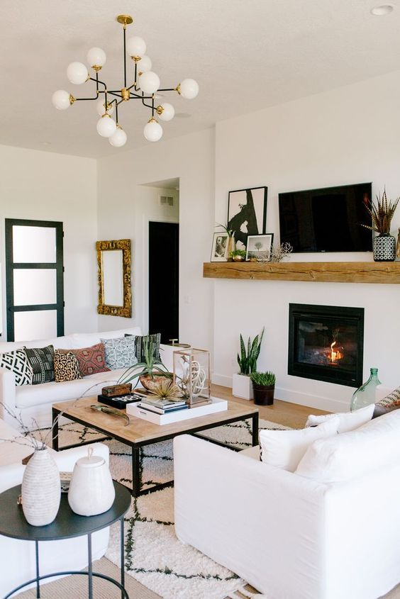 an elegant modern living room with a built-in fireplace, white sofas, a chic chandelier, a low coffee table and some artworks and mirrors