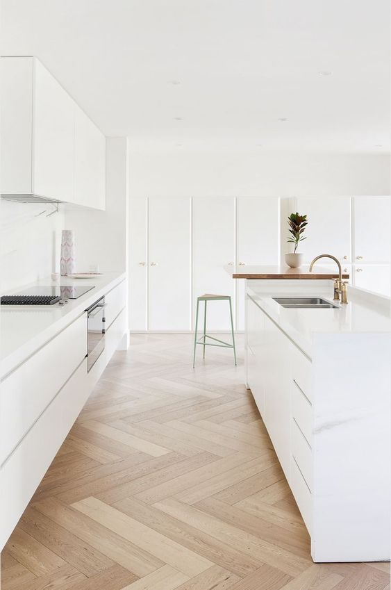 an exquisite minimalist kitchen in white with neutral parquet flooring, built-in appliances is a chic and very beautiful space