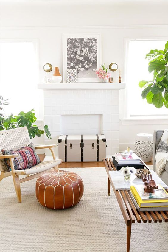 an inviting summer living room with a faux fireplace, a woven chair, a wooden bench, a leather pouf and potted plants