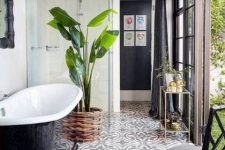an outdoor-indoor bathroom with neutral walls and mosaic tiles on the floor, a black bathtub, a black chair and a potted plant