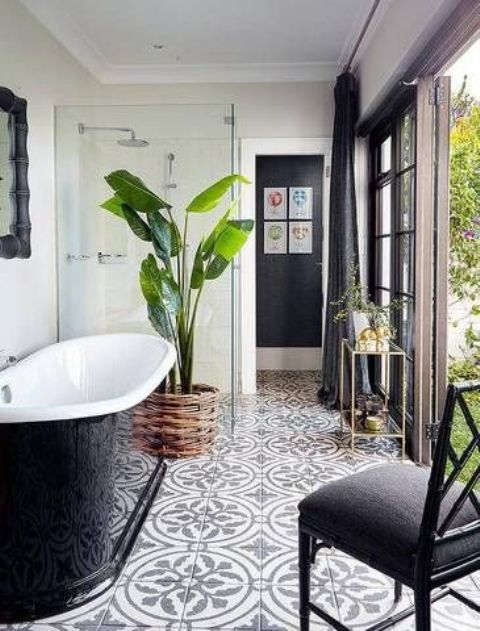an outdoor indoor bathroom with neutral walls and mosaic tiles on the floor, a black bathtub, a black chair and a potted plant
