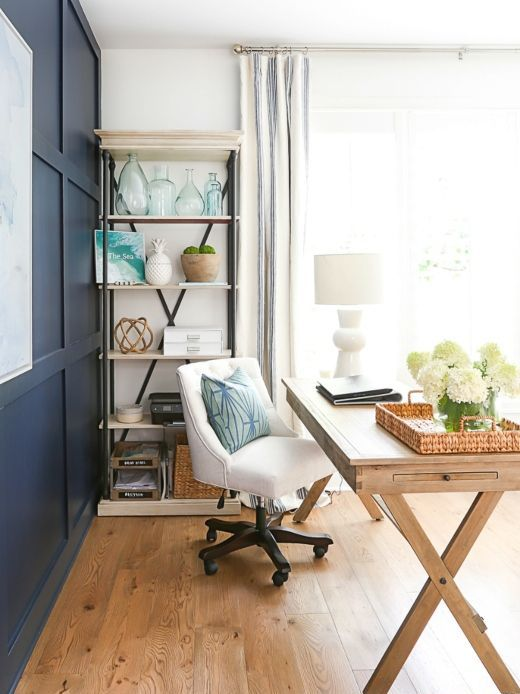 coastal farmhouse home office with a navy paneled wall, a wooden trestle desk, a white upholstered chair and a storage unit