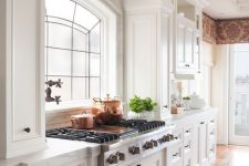 02 a beautiful vintage kitchen in creamy shades, a large cooker and a hood over the space that seems part of a cabinet