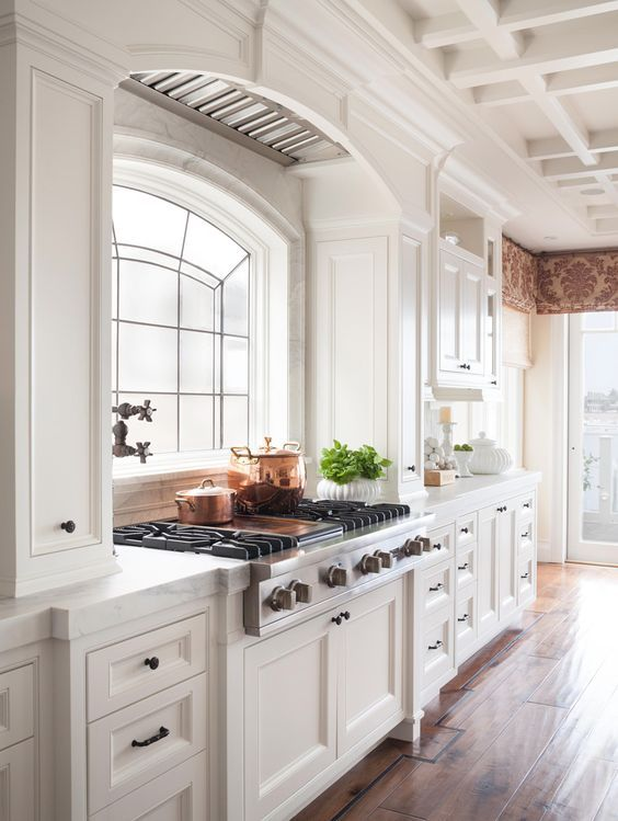 a beautiful vintage kitchen in creamy shades, a large cooker and a hood over the space that seems part of a cabinet