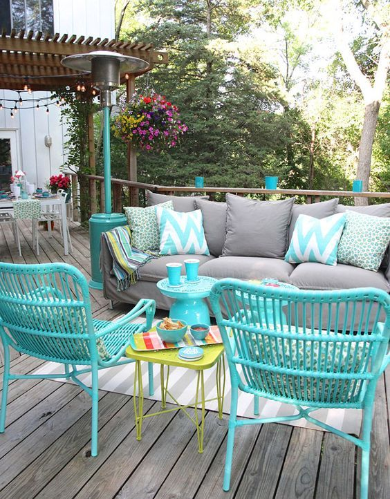 a bright outdoor living room with a grey sofa, turquoise rattan chairs, a green side table and some colorful cushions and pillows