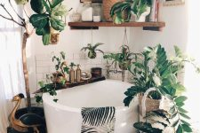 02 a gorgeous boho bathroom done with various neutral tiles and with a soak tub surrounded with potted plants and with a gallery wall