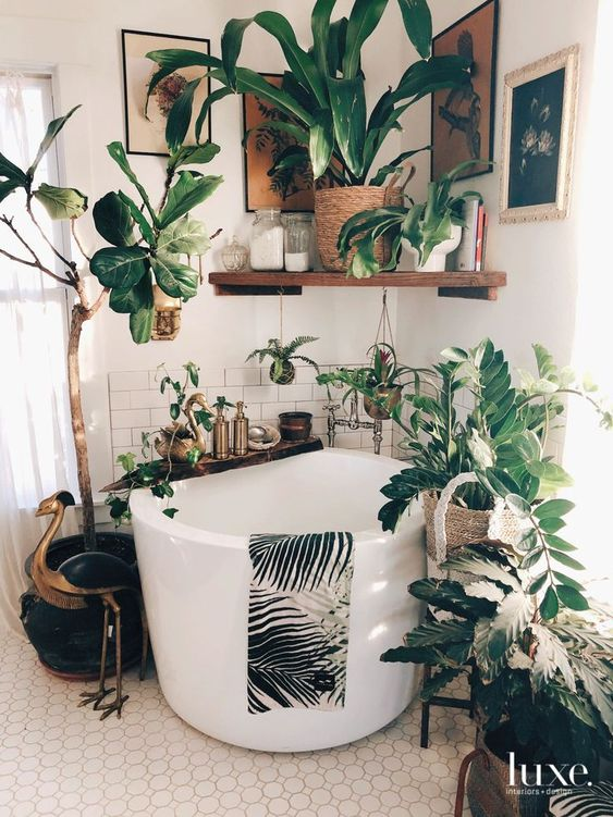 a gorgeous boho bathroom done with various neutral tiles and with a soak tub surrounded with potted plants and with a gallery wall