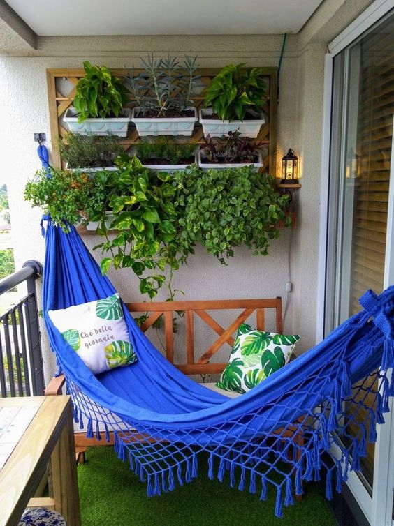 a small balcony with artificial grass, a bold blue hammock, potted herbs and simple wooden furniture with pillows