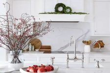 a beautiful white kitchen with a hood that merges with the wall and cabinets, a kitchen island with a white marble countertop