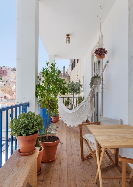 a boho balcony with simple wooden furniture, potted greeneyr, a white hammock with detailing is a lovely space to relax in
