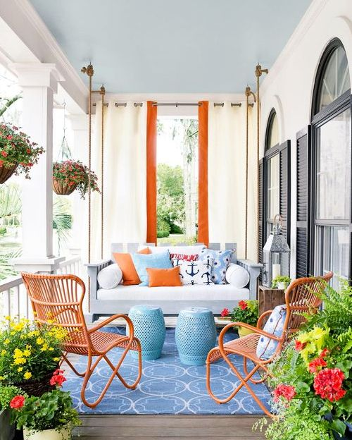 a bold coastal porch with a hanging sofa with bright pillows, blue side tables, orange rattan chairs, potted plants and blooms is fun and cool