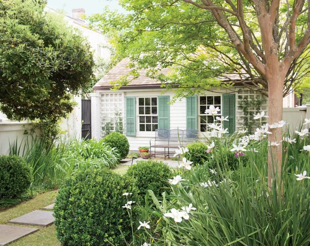 a cozy small cottage backyard with grasses and simple blooms, with a metal bench and potted plants is a very cozy and inviting space