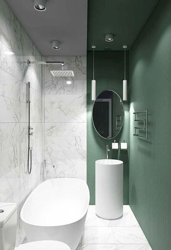 a gorgeous minimalist bathroom with white marble tiles and a green accent wall that brings this space to life