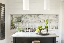 04 a catchy kitchen with white cabinets and a grey kitchen island, a marble backsplash with shelves and an integrated kitchen hood