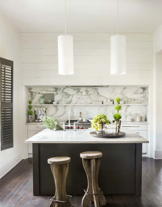 a catchy kitchen with white cabinets and a grey kitchen island, a marble backsplash with shelves and an integrated kitchen hood