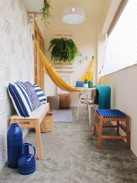 a colorful balcony with a yellow hammock, a bench, chairs and stools with bold blue printed textiles, blue vases and greenery