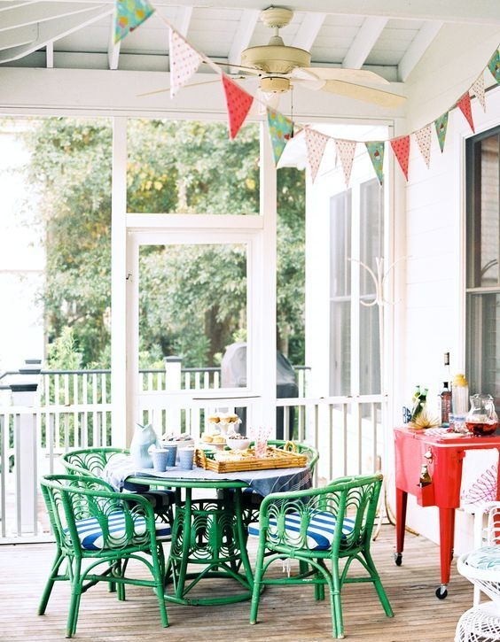 a colorful outdoor space with green rattan furniture, colorful cushions, bold banners and a colorful cart