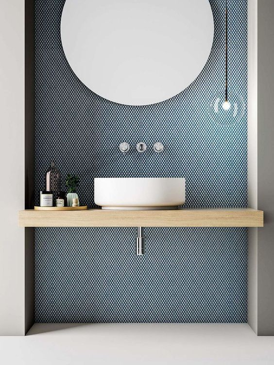 a minimalist bathrom with a blue penny tile accent wall, a wooden vanity and a round sink plus a large round mirror