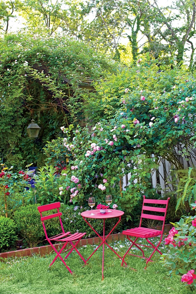 a small and cozy backyard with grass, with a hot pink outdoor dining set, with lots of blooming branches and blooms is cool