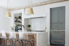 05 a chic kitchen in white, with a hidden hood, a large kitchen island clad with white marble and pendant lamps