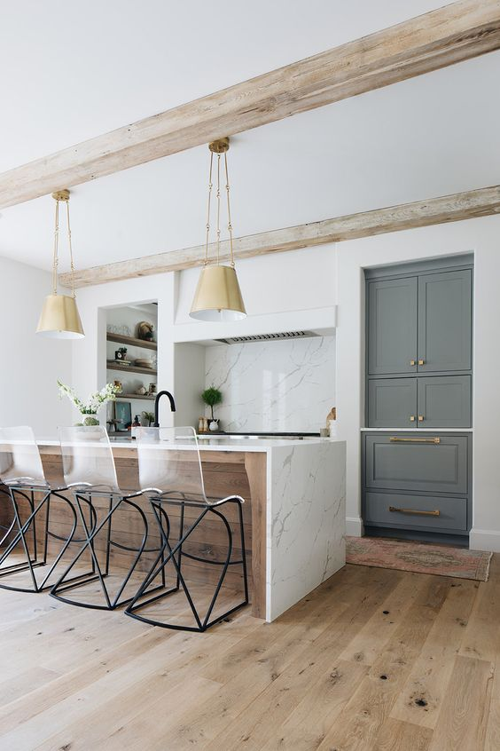 a chic kitchen in white, with a hidden hood, a large kitchen island clad with white marble and pendant lamps