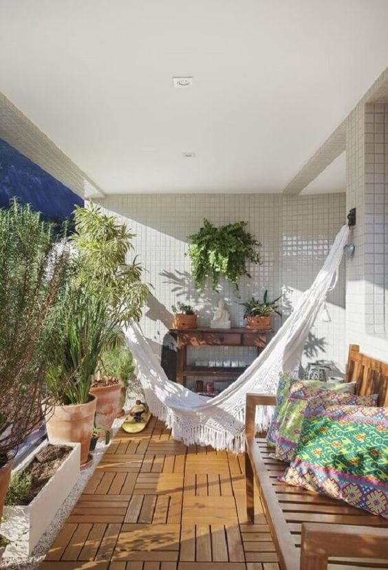 a cool balcony with potted shrubs and greenery, with a macrame hammock, a wooden bench with colorful pillows