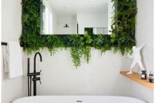 05 a small contemporary bathroom with all neutral everything, with a mirror surrounded with fresh greenery looks cool