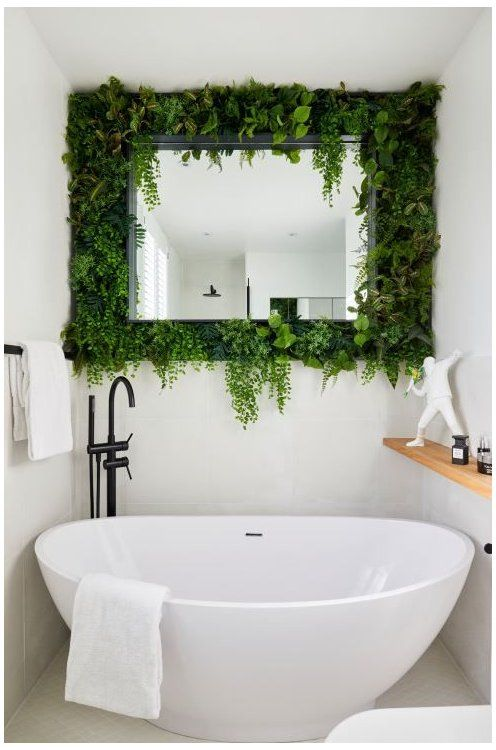a small contemporary bathroom with all neutral everything, with a mirror surrounded with fresh greenery looks cool