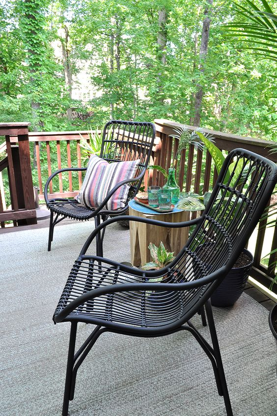 black rattan chairs, a tree stump stool with drinks and some greeneyr around to organize a cool outdoor sitting space