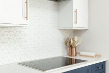 06 a chic kitchen with navy lower cabinets and upper white ones, with a white geometric backsplash and a hidden hood plus copper touches