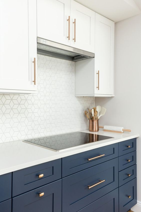 a chic kitchen with navy lower cabinets and upper white ones, with a white geometric backsplash and a hidden hood plus copper touches