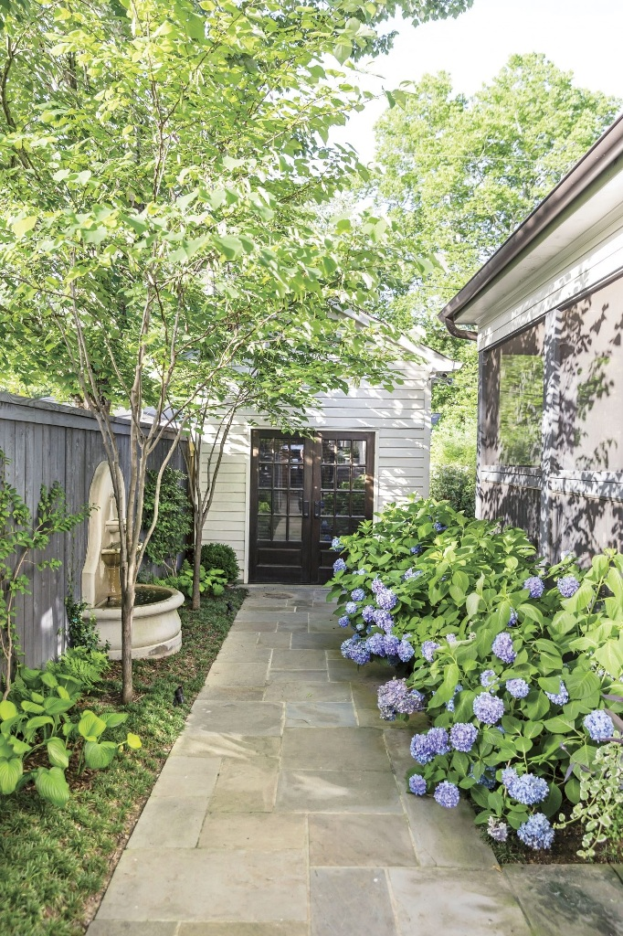 a small backyard with greenery and a small fountain, with lush florals lining up the wall of the house is a dreamy space