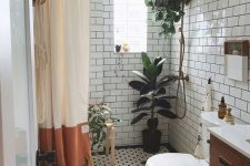 06 a small neutral bathroom with white subway tiles and black and white penny ones, with potted plants and a stained vanity