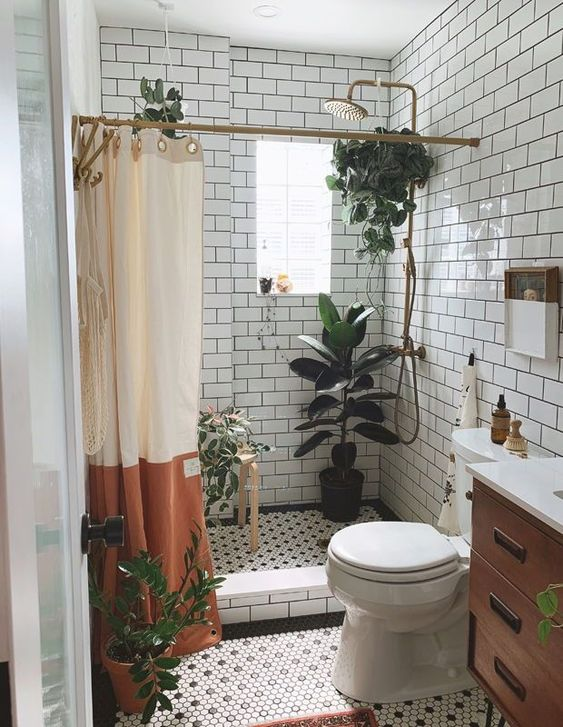 a small neutral bathroom with white subway tiles and black and white penny ones, with potted plants and a stained vanity