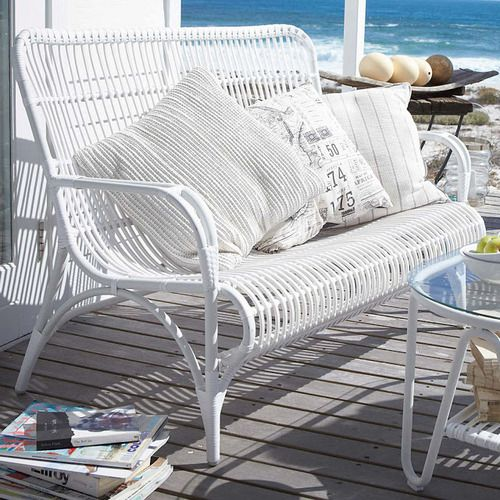 a white rattan bench with printed pillows and a table, with a view of the sea and a stack of books