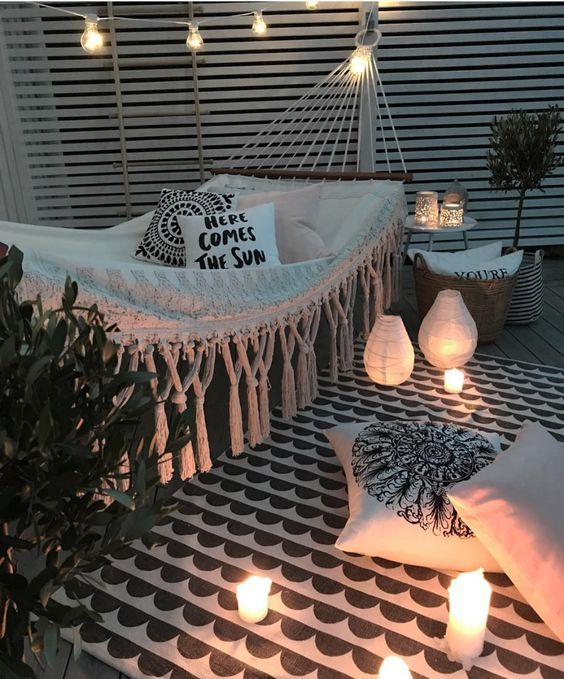 a black and white patio with a fringe hammock, printed textiles, lots of candles and candle lanterns and potted plants