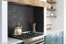 07 a chic kitchen with teal shaker cabinets, a black cooker and a black tile backsplash plus a hidden hood with a rough wooden panel