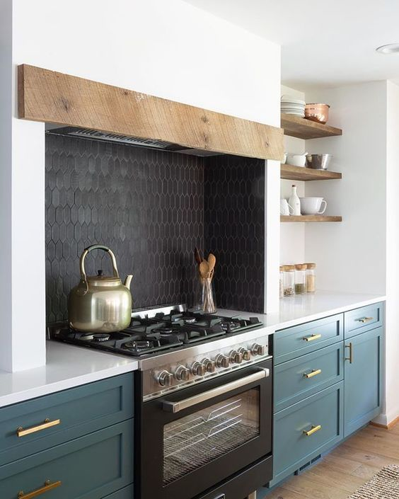 a chic kitchen with teal shaker cabinets, a black cooker and a black tile backsplash plus a hidden hood with a rough wooden panel
