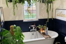 07 a small and cool bathroom with white walls and black paneling, a mosaic floor, potted plants hanging over the tub