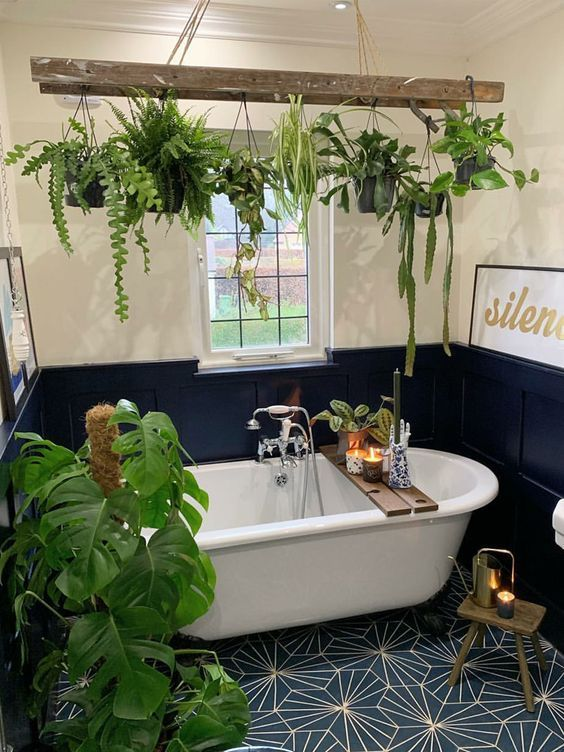 a small and cool bathroom with white walls and black paneling, a mosaic floor, potted plants hanging over the tub