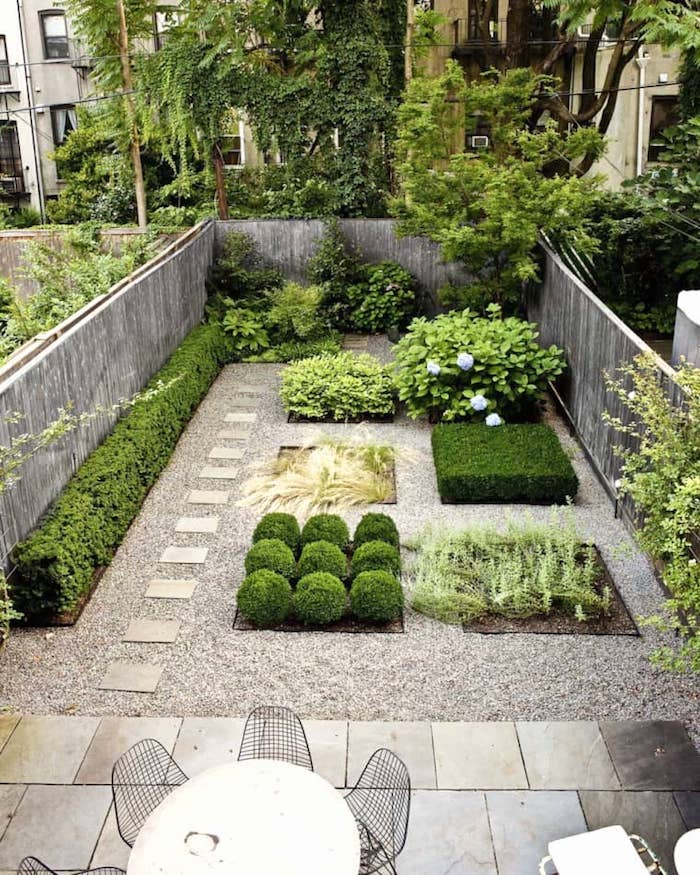 a small backyard with mini flower beds with different types of plants and gravel and tiles around is pure modern elegance